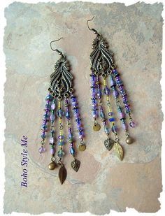 These long, exotic Boho gypsy assemblage earrings are created with a variety of peacock color glass beads, amethyst dangles, lavender glass pinch beads, Toho glass seed beads and sparkling iridescent crystal beads. Antique brass is used throughout, including detailed Bohemian, feather like components, various brass spacers, gypsy bells and charms. Each strand has its own exclusive set of hand assembled treasures. Combined, these strands create unique, romantic boho earrings that you will…