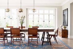 Angular interactions between contemporary chairs and a large farm table contrast with shapely, swirly glass pendant lights to make this modern dining room feel masculine and suave.