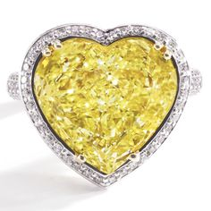 FANCY VIVID YELLOW DIAMOND RING, CHRISTOPHER DESIGNS The heart-shaped modified brilliant-cut diamond of fancy vivid yellow color weighing 10.05 carats, framed by round diamonds, mounted in platinum and 22 karat gold, size 6½, signed Christopher, numbered K6036.