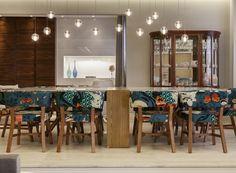 Na sala de jantar, o destaque são as cadeiras personalizadas com tecido da estilista Adriana Barra. Mesa, da Estar Móveis. Os pendentes, da Bocci, criam um clima de velas suspensas sobre a mesa. Ao lado, a cristaleira que pertenceu ao avô do morador (Foto: J. Vilhora/Divulgação)