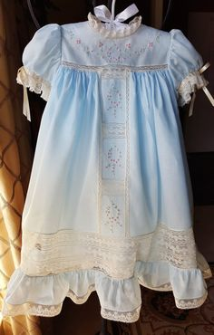 This stunning heirloom dress features a T-yoked front with beautiful pastel hand embroidery. This dress is constructed in light blue Swiss batiste with ecru French Maline and French Valenciennes laces. The front yoke has an elaborate embroidery design of pink bullion roses and bullion leaves and stems. This embroidery motif is carried down the T-yoke panel in the front. French laces further enhance the embroidery design and border/outline the embroidery.  The neckline is finished with a ...