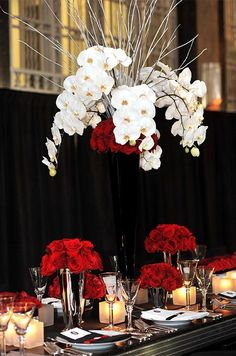 Crisp white orchids and frosted branches paired with classic red roses add drama to a black and silver table.