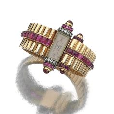 YELLOW GOLD, RUBY AND DIAMOND WRISTWATCH, 1940S. The hinged bangle of fluted design highlighted with buff-toped calibré-cut rubies, set at the front with a rectangular dial with black arabic numerals, the terminals set with cabochon and calibré-cut rubies and brilliant-cut diamonds, circumference approximately 155mm.