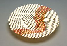 """by Ed Edwards. """"Light Amber Double Wave Round Glass Basket"""" Art Glass Bowl The kiln formed, glass basket has pale amber transparent glass strips overlaid with white and streaky amber strips to form a double wave pattern flowing across the design. The streaky amber glass includes streaks in multiple shades of amber, brown, and white. The piece is then fused and slumped to create the basket."""