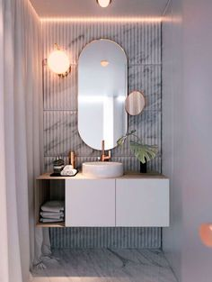 An oval mirror is hot and extra stylish with a slim brass frame like here.