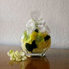Beautiful yellow roses with other silk flowers in a sealed glass. The flowers are in clear liquid soap. The soap is used to suspend the flowers.