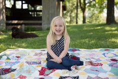 Sweet little girl pose on vintage quilt outside