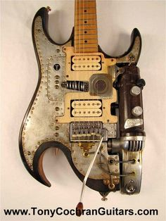 """Jynx Electric Guitar by Tony Cochran This electric guitar is twice jinxed. Andrew """"Fish"""" Cook bought a charred guitar body from a street vendor in Arkesden, Essex in 1994. The seller claimed it had been salvaged from a 1991 house fire where a famous Rock musician perished. The entire right side had been burnt to a crisp, so Andrew fashioned a prosthetic control area using a 1949 Sunbeam hedge trimmer his uncle had given to him in a box of junk. Sometime in ..."""