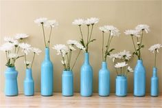 Different size and shaped glass bottles painted with daisies for a centerpiece...Cheap & Chic :-)