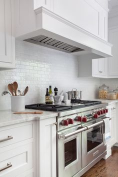 Lovely white kitchen features white shaker kitchen cabinets paired with calcutta marble countertops and a white gloss mini subway tiled backsplash flanking a white paneled hood over a Wolf Range.
