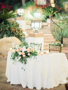 sweetheart table with an overhanging floral arrangement and flowers on the chairs.