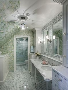 Floral wallpaper, a sloped ceiling and a pendant light fixture give this traditional bathroom a romantic feel. The green and white mosaic-tile floor, white furnishings cabinetry and double console sink round out the look.