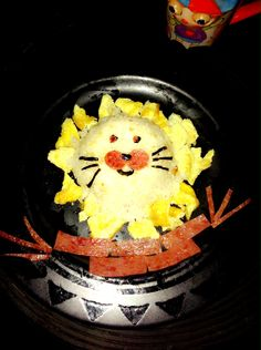 Rawr!!! Bento... Rice sitting on scrambled egg and some ham on the sides :)