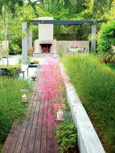 outdoor fireplace. modern pergola. hurricane lanterns along linear path flanked by grasses and heuchera