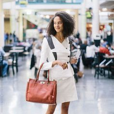 A woman in a white suit holding a bag and a newspaper by stalmanandboniecka | Stocksy United