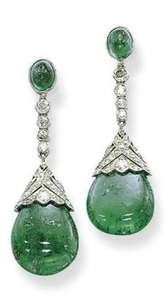 A PAIR OF ART DECO EMERALD AND DIAMOND EAR PENDANTS, CIRCA 1920. Each suspending an emerald drop with a pierced single and circular-cut diamond cap, from a diamond collet line to the oval emerald surmount, mounted in platinum, 4.7 cm long. #ArtDeco