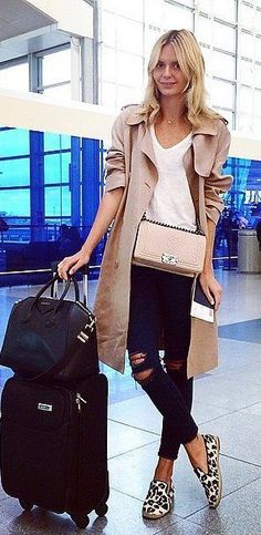 A camel trench coat, t-shirt, distressed jeans, leopard loafers, and a Chanel bag.