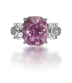 A COLOURED SAPPHIRE AND DIAMOND RING   Set with a cushion-shaped pink sapphire, weighing approximately 8.07 carats, flanked on either sides with cushion-shaped diamonds, weighing approximately 1.03 and 1.00 carat, to the graduated brilliant-cut diamond shoulders, mounted in platinum