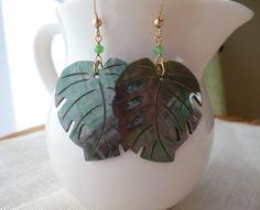 ☆黒蝶貝をモンステラの葉の形に型抜きしたものです。 貝特有の虹色の輝きが美しいピアスです。 裏面はツルンとしています。 トップの天然石はクリソプレーズのボタン...|ハンドメイド、手作り、手仕事品の通販・販売・購入ならCreema。