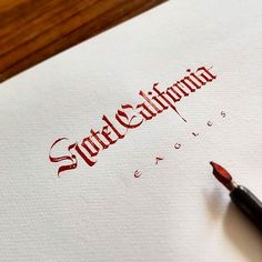 Gothic calligraphy practice on textured watercolor paper with steel nibs and red…