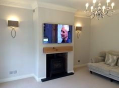 Smart TV wall mounted television over a log burner. Because of the intense heat from the fire we have installed a piece of re-claimed timber just below the TV. All the HDMI cables and electric feed have been concealed in the wall and we have re plastered. The customer had painted over now and the finished job does look very good.