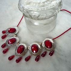 Collier rouge rubis esprit art déco. Les cabochons sont en métal argent et verre couleur rouge. Quelques gouttes en verre rouges allègent l'ensemble. Une chaine de prolongation, terminant un fin cordon rouge, permet de le porter à différentes longueurs.