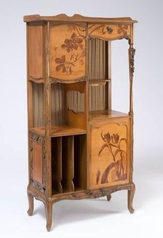 Louis Majorelle's furniture received international acclaim at the 1900 Paris Exposition Universelle at which he showed furniture with landscape and flower designs described in marquetry (inlaid wood) or carved into polished, luxurious woods. The following year Majorelle was involved in the formation of the Ecole de Nancy (with Emile Gallé as president) to promote the role of the arts in industry and Nancy as a centre of production for Art Nouveau. UEA 21004 - Etagère, Louis Majorelle