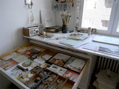 One day I would love to have an art studio in my home. I love this broad desk with the wonderful wide drawers for all sorts of art materials! I love that the desk is right in front of a large window too!