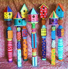 Hand-painted birdhouses affixed to spindles. The only issue? These look like craft store houses (which don't open for cleaning) so do this with functional bird houses instead!