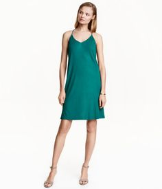 Teal. Short dress in crêped viscose with a sheen. V-neck and narrow shoulder straps. Lined at top.