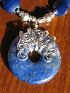 Artist: Tareen Rayburn  Description: A beautiful hand wrapped lapis donut wrapped with sterling silver copper filled wire. The chain is made with lapis and silver beads,coin shaped and flat oval.