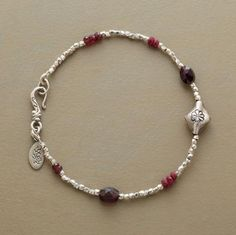 """Garnets stand out amongst the glimmer and glow of faceted sterling silver beads. A hand stamped bead adds a floral flourish. Hook clasp. Exclusive. Approx. 7-1/2""""L."""