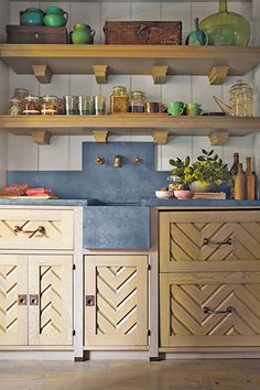The chevron panels in these guesthouse kitchen cabinet fronts were inspired by doors designer Steven Gambrel saw in Virginia, where he studied architecture in college. Their graphic lines give the small space major decorative appeal. The open shelves above, with their stepped-block brackets, and the simple paneled wall behind, add supporting layers of interest and detail.