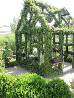 I'm thinking this wouldn't be too hard for a handy person. Build the frame, cover in chicken wire and plant vine type plants, maybe ivy. I like this a lot!