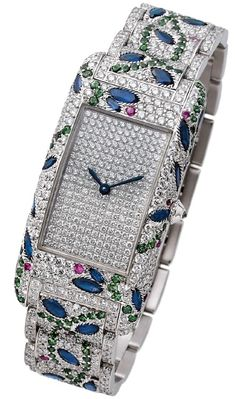 Charles Oudin Full Amazone Curvex Watch- Sapphires, Rubies and emeralds make up a floral motif in the landscape of diamonds. In total the watch has 26 carats of precious stones.