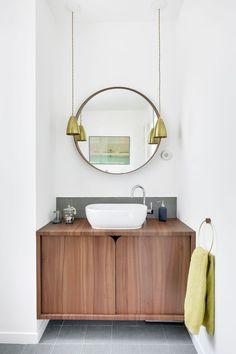 Lui aussi dessiné par Margaux Meza et Carla Lopez, le meuble vasque en stratifié noyer adopte des lignes rétro chic, adoucies par l'arrondi du miroir Ikea.