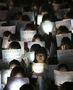 Students hold papers with candles as they pray for the safe return of their friends aboard the sunken ferry Sewol at Danwon High School in Ansan, south of Seoul, South Korea, Friday, April 18, 2014. (AP Photo/Yonhap) KOREA OUT ▼18Apr2014AP|Captain of sunken S. Korean ferry, 2 crew arrested http://bigstory.ap.org/article/rescuers-rush-reach-hundreds-skorean-ferry