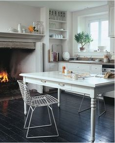 what a wonderful kitchen. The table, the chairs ...the fireplace. dreamy.