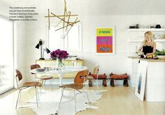 rug + tulip table + modern chairs + white walls + bright art + striking lighting