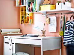 Un rincón de estudio en el salón compuesto por un escritorio, una silla y armarios de pared de IKEA.
