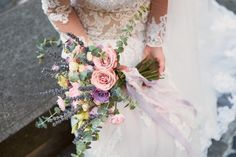 Close-up of pink and violet wedding bouquet in bride's hands Free Photo