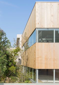 Bands of timber alternate with slices of glazing across the facade of this Tokyo house