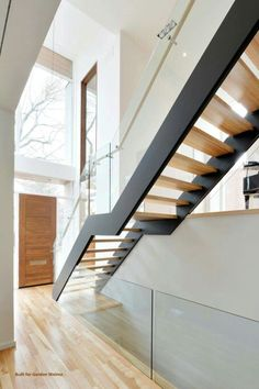 Freestanding stair with metal stringers, open risers and glass railings. By Accurate Stairs and Railings.