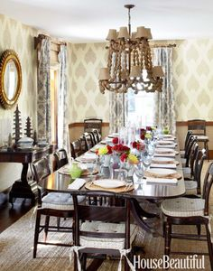 The dining room's coconut-shell chandelier, paisley wallpaper, and soapstone pagodas cast an exotic spell on a crew of antique Hitchcock chairs. Click through for more interior design inspiration from designers' summer homes.
