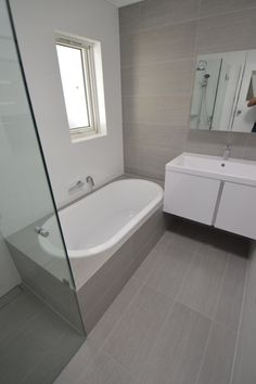 Bayswater bathroom renovation completed October 2013. Frameless shower screen w/gully drain. Large floor tiles on bath hon and up wall for classic feature. You can view our walkthrough of this on Youtube.