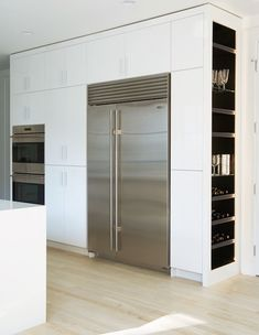 Modern kitchen features a full wall of pantry cabinets fitted with double ovens and a stainless steel refrigerator and freezer alongside end cabinets lined with shelves housing wine glasses and wine bottles. around refrigerator ideas Kitchen Pantry Cupboard, Kitchen Pantry Cabinets, Kitchen Shelves, Glass Shelves, Wall Pantry, Oven Cabinet, Kitchen Storage, Kitchen Island, Living Room Kitchen
