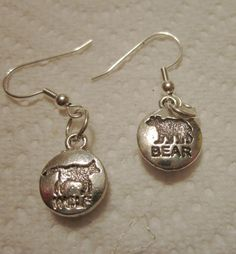 Mismatched earrings of bear and wolf - silver plated with paw print on opposite side.  $10 .