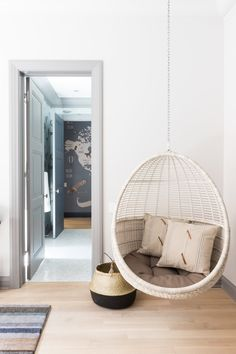 Kate Marker Interiors - Emily Kennedy Styling & Photography - Over blond wood floors, a rattan hanging chair hangs beside a black dip-dyed wicker basket.