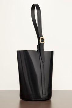 new bucket bag... more avant-garde.  a slightly geometric shape, somewhat shiny finish, a single belt-like strap.  by Trademark