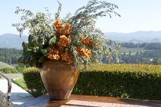 mediterranean floral arrangement created with orange cymbidium orchids, olive leaf and magnolia. Atelier Joya event design and florals San Francisco